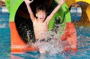 A boy enjoying a slide at a waterpark.