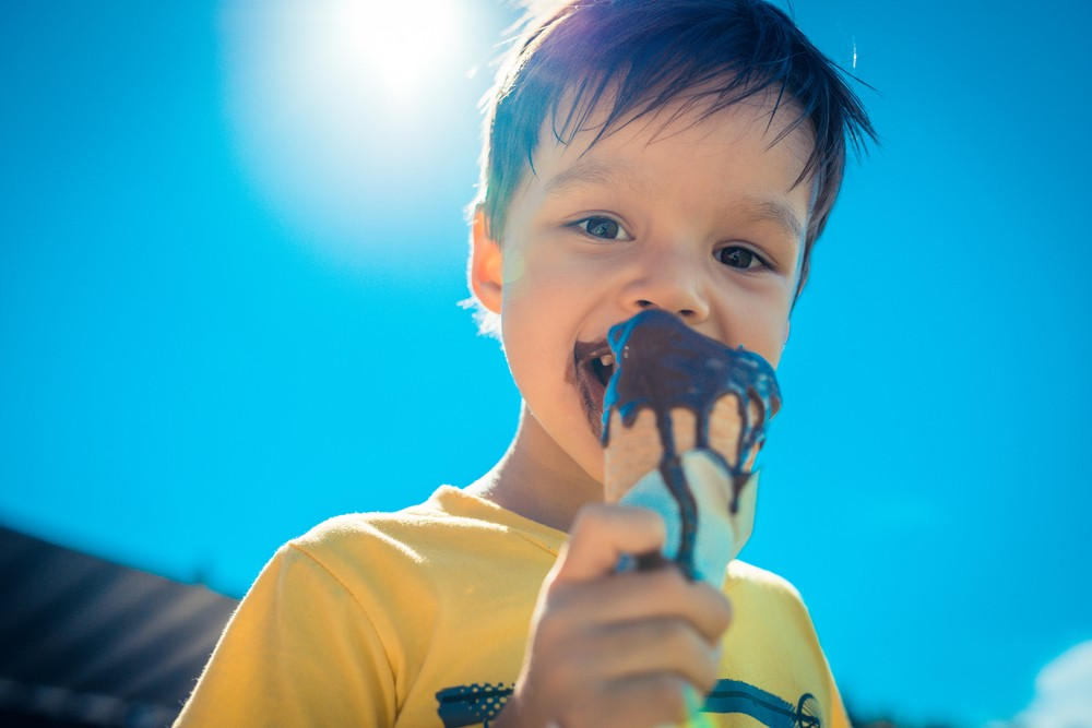 A boy enjoying a chocolate ice cream cone in the sun.