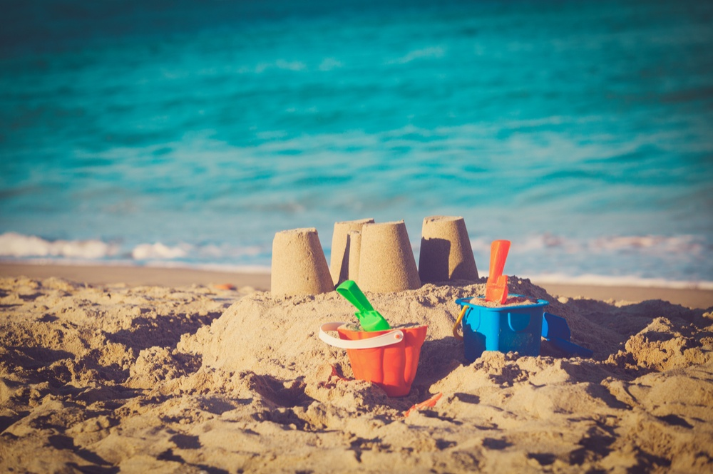Sandcastles with small plastic buckets and shovels